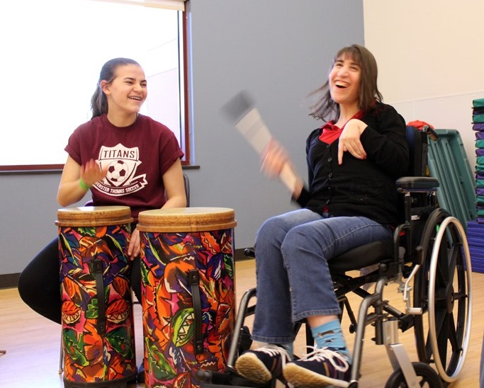 Two young women drumming and smiling