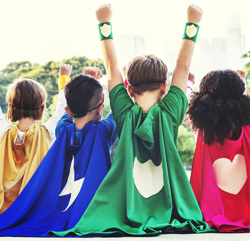 Photo of diverse group of four children from the back - all are wearing superhero capes and one has their arms raised