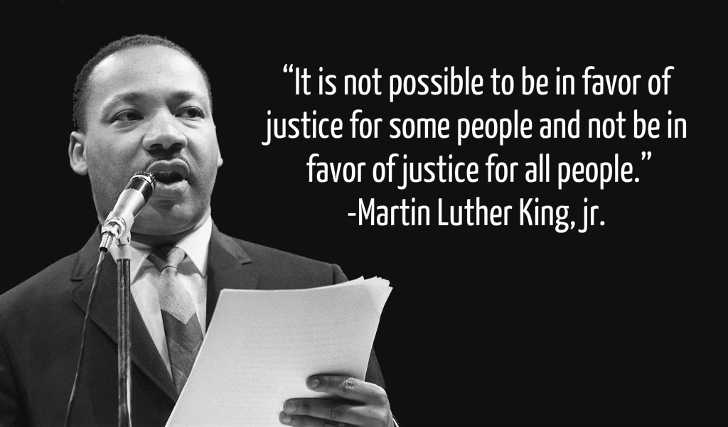 Martin Luther King Jr stands in front of microphone and text shows quote about importance of justice for all