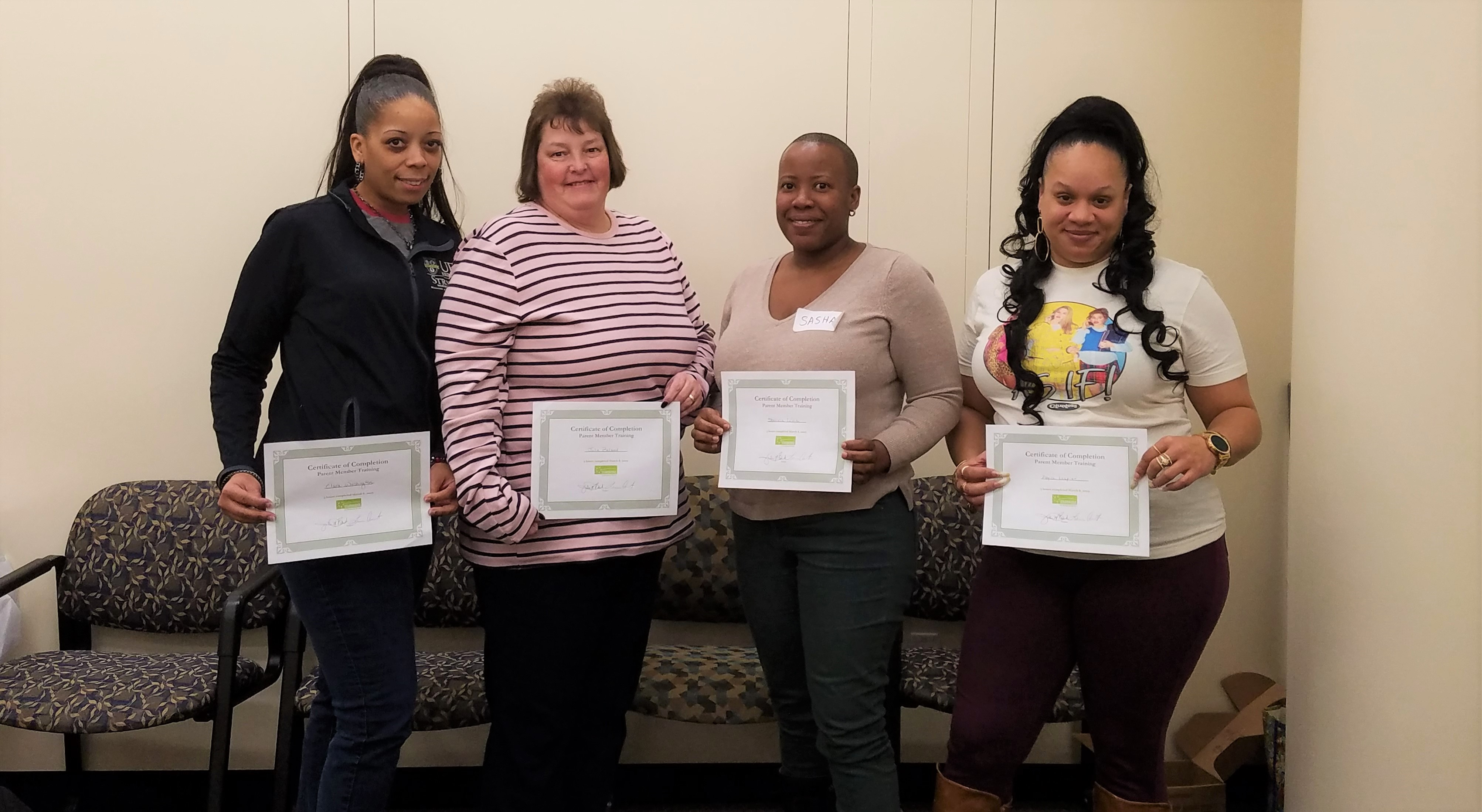Four adult women of diverse races holding certificates of completion from a Starbridge workshop series