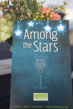 Photo shows program book of Among the Stars in front of floral arrangement